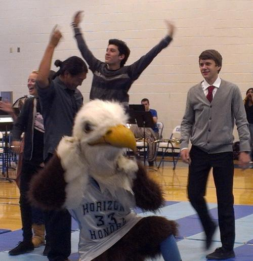 Luis Quintanilla and Daniel Quan, grade 12, and Kyle Bonowski, grade 10 and celebrate with the eagle at the Homecoming Pep Rally.