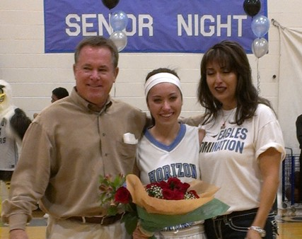 Senior Gina Garvey poses with her parents before the Valley Christian game.