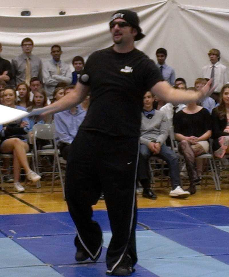 Mr. Schneider shows school spirit by helping Varsity Girls' Basketball Coach Mr. Agostini during the pep assembly.