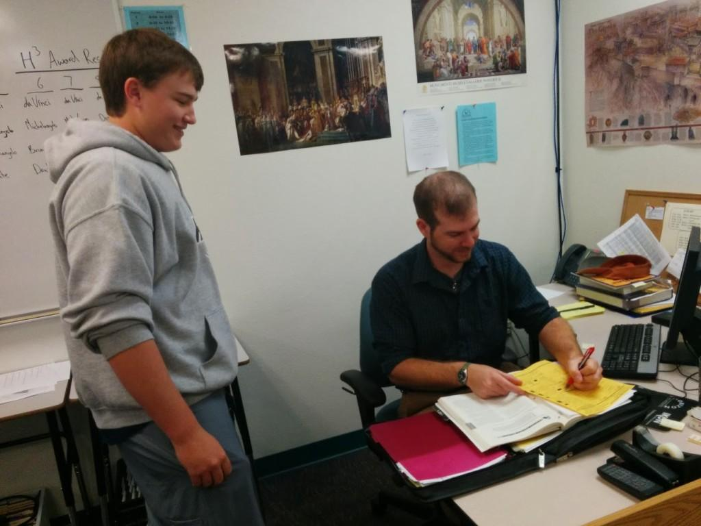 Huber signs a scheduling sheet for a student. He will be teaching World History classes at Horizon Honors.