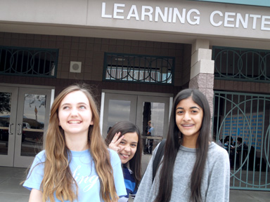 Eighth graders Ella Coste and Roshi Patel pose in front of the Learning Center while being photobombed by seventh grader Jessica Espinoza. All three girls plan to continue at Horizon Honors for high school.