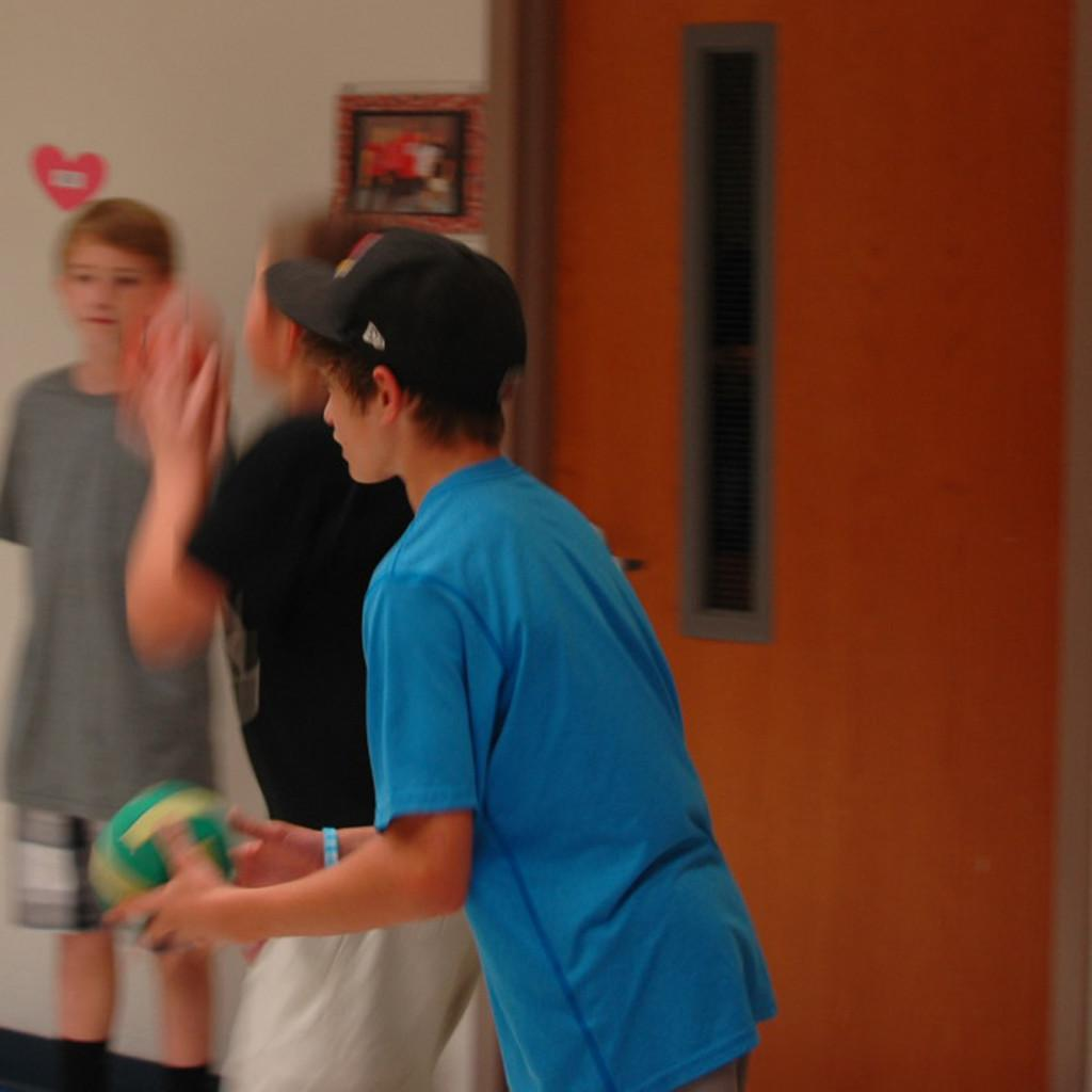 Seventh grader Preston Asher plays basketball in the hallway outside of the multipurpose room during the Middle School third quarter social. More people were inside enjoying the music and food.