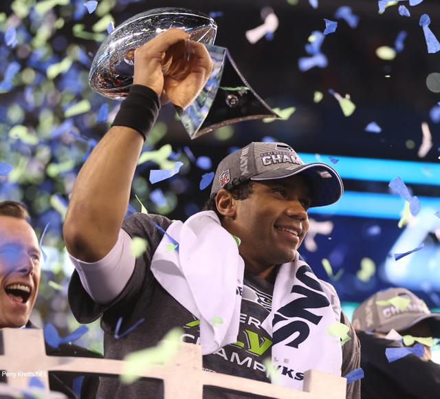 Young quarterback Russell Wilson holds the Vince Lombardi Trophy. The score results for the Super Bowl XLVIII ended up to be 43 to 8, in favor of the Seahawks.