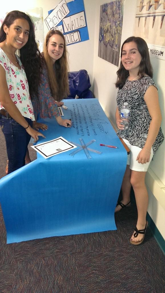 High schoolers Krista Santacruz, Alexa Geidel, and middle schooler Tessa Jung write the Resolution of Respect on butcher paper that will serve as a