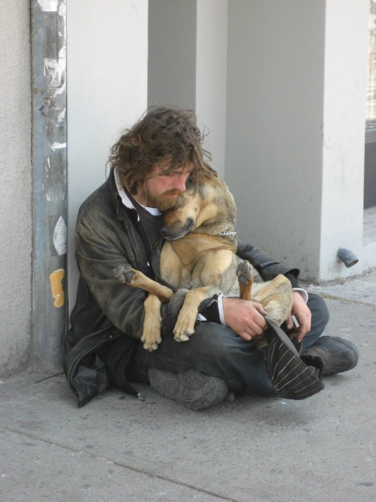 This homeless man is sitting with his dog, his only companion, his best friend.