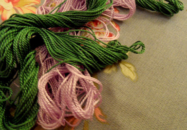 A pile of colorful embroidery floss is resting on a piece of floral fabric. Embroidering may appear difficult, but is easy to master once you know the basic stitches.