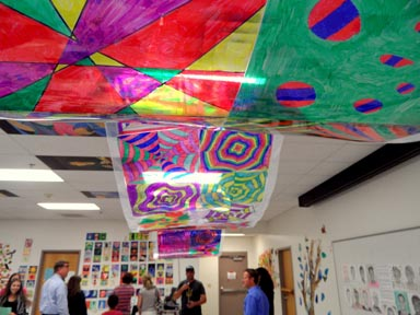 Students and their families stand under a colorful laminated 
