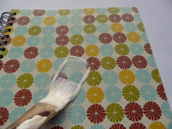 2) Paint one layer of Mod Podge over the whole notebook, and carefully smooth the pictures over it. Go slowly and carefully to avoid wrinkles.