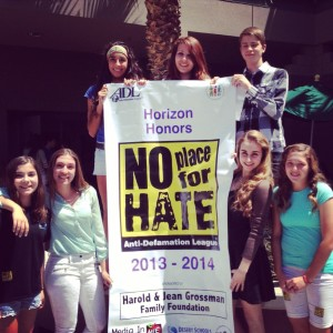 (L to R) Seventh grader Tessa Jung, freshmen Karolina Grgurovic, Krista Santacruz, sophomores Kori Klein, Wesley Jamison, junior Alexa Geidel, and seventh grader Finley Lindsey pose with the official No Place For Hate banner.  It declared Horizon Honors as a member of the national organization and the first charter school in Arizona to receive the recognition.