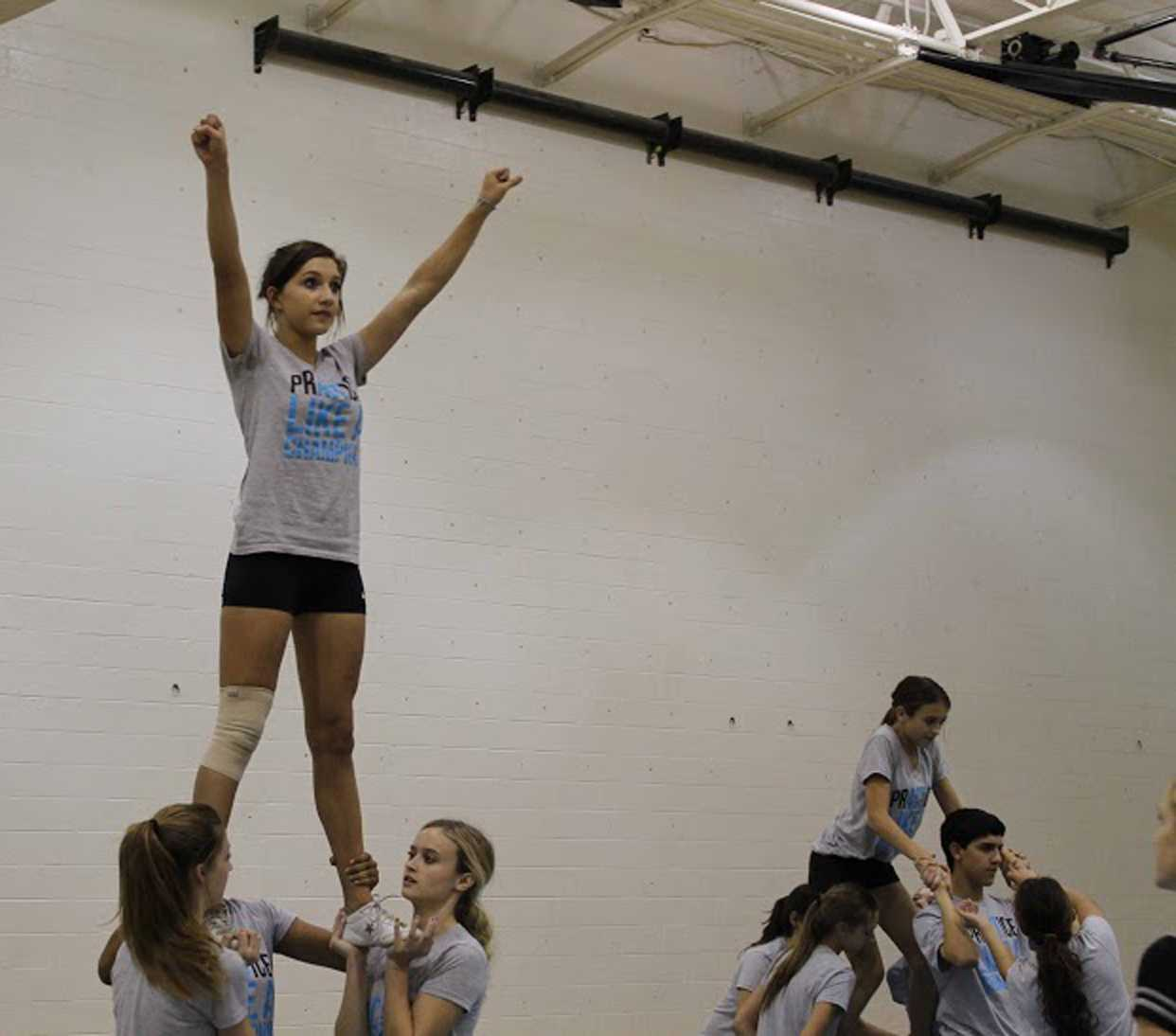 Junior Natori Cruz, freshman Haley Greene, and juniors Madison Page and Bree Lientz practice stunts at their Spiritline Stunt Clinic.