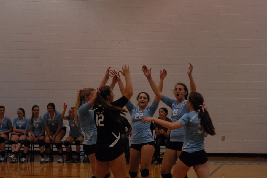 Varsity Volleyball players come together to celebrate scoring a point. The Varsity team won three matches in a row to defeat Williamsfield.