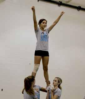Junior Natori Cruz, freshman Haley Greene, and juniors Madison Page and Bree Lientz practice stunts at their Spiritline Stunt Clinic.