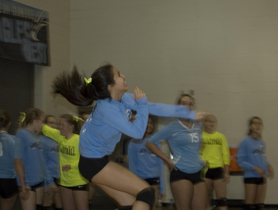 Sophomore Tiana Oster smashes a jump serve during warm-ups. The Eagles pre-game routines are almost as entertaining as the game themselves.