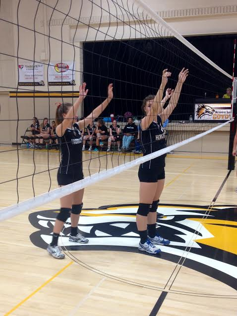 Freshmen Gretchen Hoefer and Hannah Glew stand positioned at the net, waiting for a play to begin.
