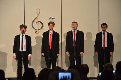 """(L to R) Sophomores Joey Vitagliano and Zane Greenawalt, and seniors Bennett Wood and Sean McElrath perform """"Walk Like a Man,"""" which they arranged and was choreographed by senior Alexa Geidel."""