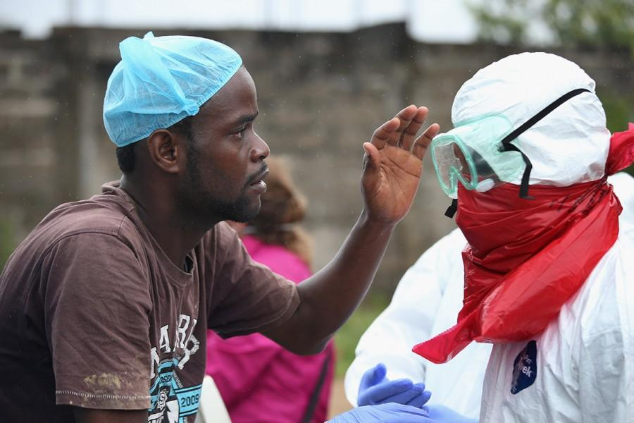 A Liberian man, part of a local aid team, helps a fellow worker put on a protective suit. Clothing such as this must be worn at all times to prevent workers from exposure to the virus.