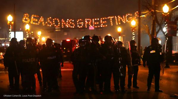 "People riot in Ferguson after court decision to give officer Darren Wilson a paid leave for shooting teenager Michael Brown. Police congregate in front of a street decoration saying ""Seasons Greetings."""