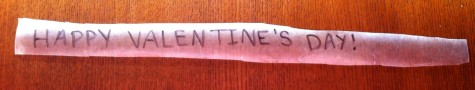 "9. While your treats are setting, write a message on a strip of wax paper. I used the phrase ""Happy Valentine's Day,"" but you can personalize it to be more sentimental."