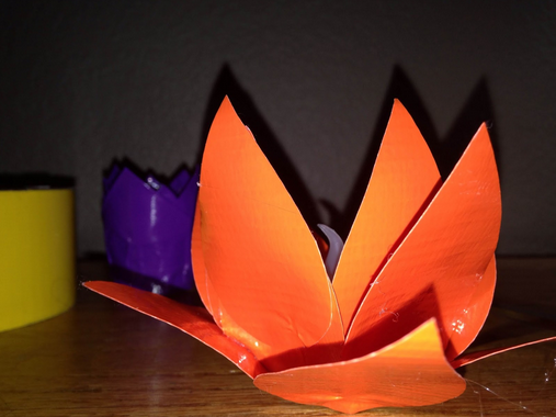 Repeat all around the flower, layering the petals where you like in order to create a lotus-like figure. You may have to bend the duct tape toward the outside of the candle to prevent the petals from just sticking straight up, but it should bend willingly. With that, the lotus is done!