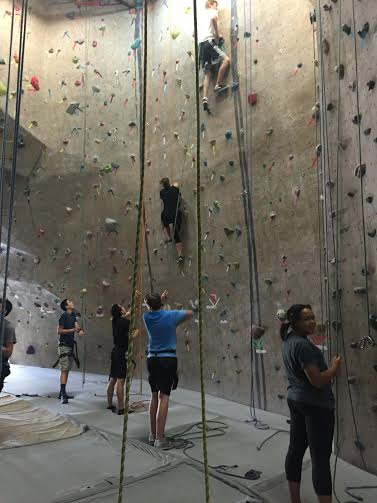Two students climb one of the many walls with ease as their partners control the belay.