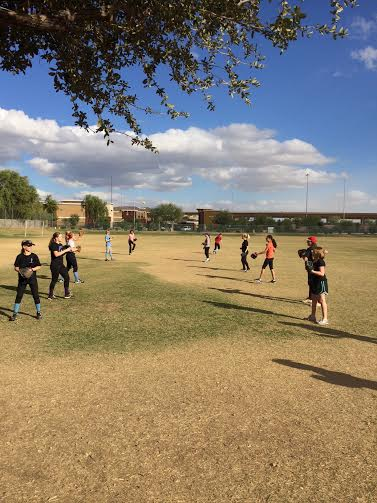 The people who are trying out for softball get ready by warming up.