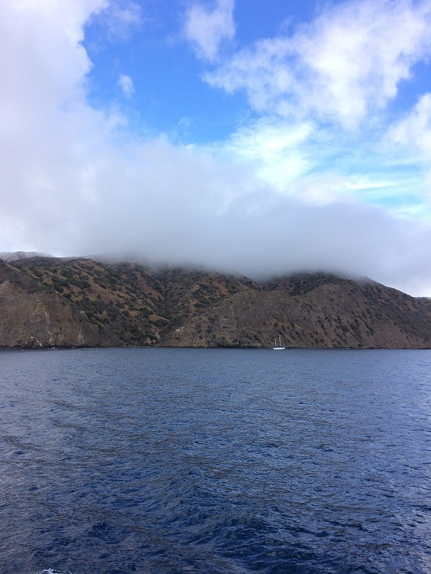 Clouds cover the top of the mountains on the island.