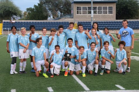 The soccer team poses with their first place plaque.